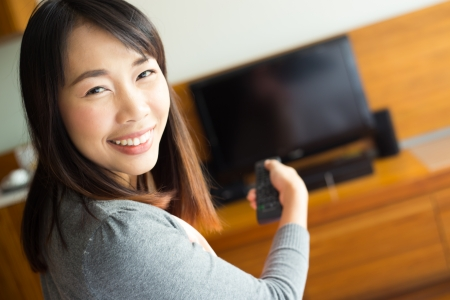 Woman with remote control switching channels photo
