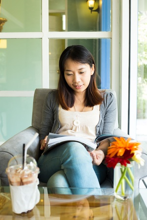 Woman reading a book on sofa in cafe restaurant photo