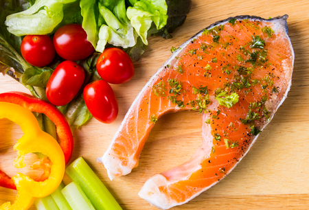 Raw fresh Salmon steak on wood  cutting board  with vegetables photo