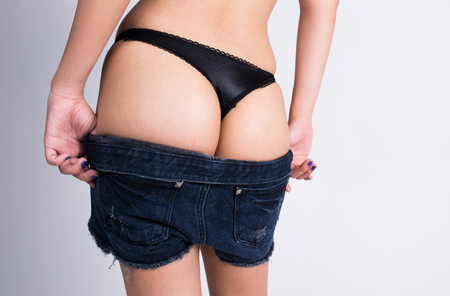 Woman take off her short jean, showing her sexy thong photo