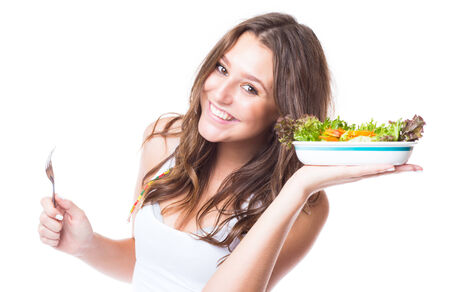 Young girl eating fresh vegetable salad on white background photo