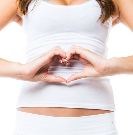 Hand in heart shaped by female hands on her stomach photo