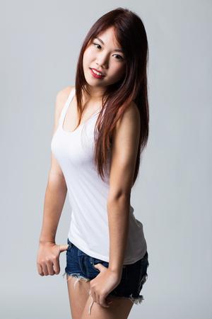Beautiful sexy asian girl wearing white shirt ans blue jean.