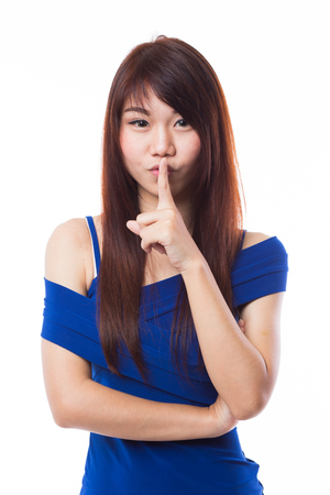 Young happy woman gesturing, hush, finger on lips, on white background photo
