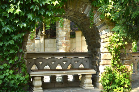 stone bench in the shade of the grapes in the arch