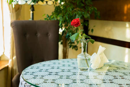 cafe interior room day time with single rose flowers on table and empty chair