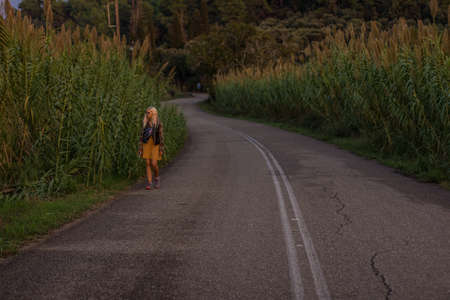 lonely young girl without home go along country side road surrounded by cereals fields
