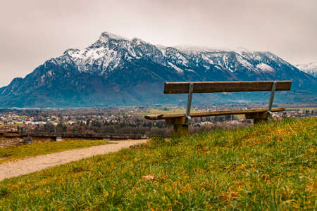 Alps mountains scenery landscape snowy range peak background with lonely wooden bench foreground beautiful view point peaceful and loneliness atmosphere in spring time