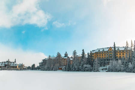 winter time hotel skying resort apartment buildings frozen lake and forest white snowy season scenic environment with cloudy blue sky background Stock Photo