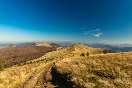 autumn time mountain ridge highland route landscape dirt trail without people blue sky background empty wallpaper copy space