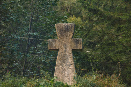 stone concrete cross religion sigh on ground hill with forest spruce needle trees dark green moody foliage unfocused background scenic view space