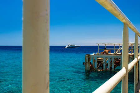 vacation beautiful destination of Red sea scenic landscape place with white pier above water resting people and cruise ship in summer season clear weather time