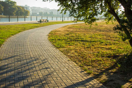 paved curved empty cycle road under trees in park outdoor country side natural environment place for rest and walking in morning fresh weather time with sun rays and light through Stok Fotoğraf