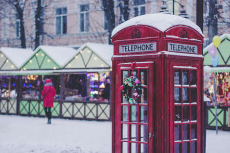 Christmas holidays concept of red classic English phone booth, season winter fair with people background in snowing weather time Фото со стока
