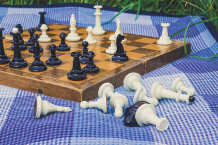 soft focus classic chess desk on background and black and white falling figures on foreground in blue carpet texture