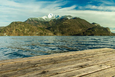 wooden deck dock foreground on lake slightly wavy water foreground scenic view unfocused mountain island lonely snowy peak background landscape empty copy space for your text