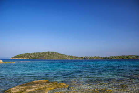 Greece beach cozy Aegean sea lagoon transparent aquamarine shallow water with horizon background view islands coast line in summer tine clear weather day copy space