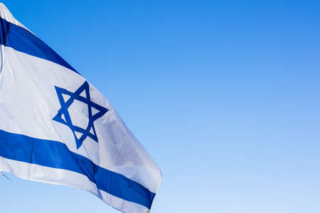 Israeli white and blue national flag with star of David evolving on a wind on empty sky background with copy space for text, political sign and symbols concept picture