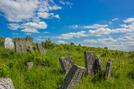 grave stone ancient cemetery vivid green grass hill land scenic landscape environment bright colorful summer day time blue sky background empty copy space for your text.