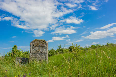 grave stone ancient cemetery vivid green grass hill land scenic landscape environment bright colorful summer day time blue sky background empty copy space for your text