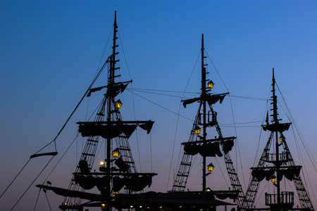 cruise vacation medieval vintage ship mast dark silhouette shape on twilight blue evening sky background after sunset with slightly lanterns illumination and empty copy space for text here