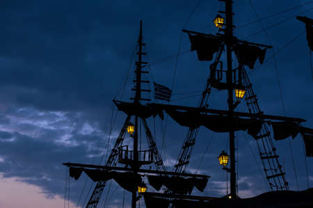 vintage ship mast silhouettes with yellow illumination of lamps on evening twilight blue sky background copy space