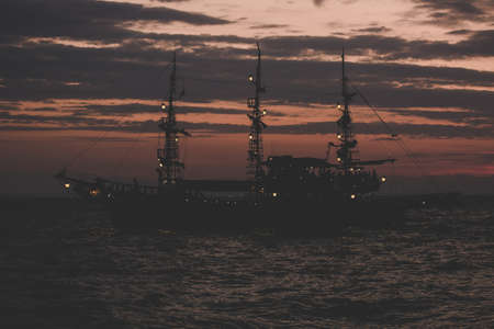 pirates concept of soft focus old vintage ship silhouette on sea water surface in romantic lighting twilight evening time after sunset copy space