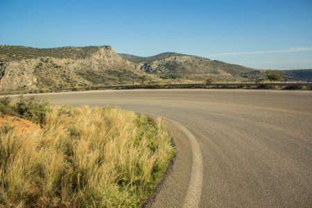 curved car road in rock mountain nature landscape in dry weather summer time Mediterranean sea district copy space