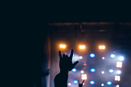 rock concept performance human hand up with fingers in music subculture sign with darkness stage colorful illumination unfocused background space for poster and copy or text here Archivio Fotografico