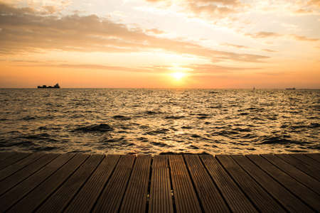 wooden deck waterfront shoreline and sea landscape horizon with ship in romantic sunset evening orange lighting time copy space for text