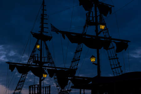 medieval old wooden ship dark mast and sails silhouette at night twilight time on cloudy sky background with many hanging lamps yellow illumination light Standard-Bild