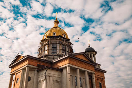 nowadays orthodox church building construction facade religion architecture stone and concrete walls exterior with pillars and gold dome photography foreshortening from below on cloudy blue sky space