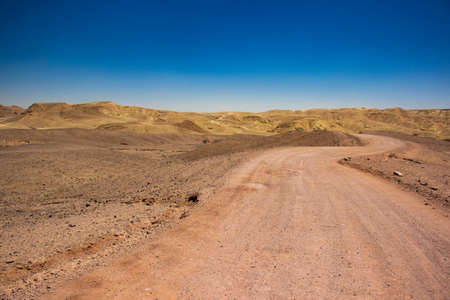 Israeli desert waste land global warming concept landscape scenic view of lonely dry ground trail ho horizon background space with sand stone mountain ridge and blue sky copy space