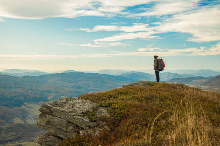 hiking mountain top edge of cliff highland scenic view with backpacker male person stay and looking side ways life style poster concept empty copy space for text here