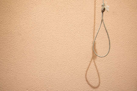human psychological problems hanging suicide concept poster picture of thread loop with shadow on soft pink textured wall simple wallpaper pattern background space for copy or your text here