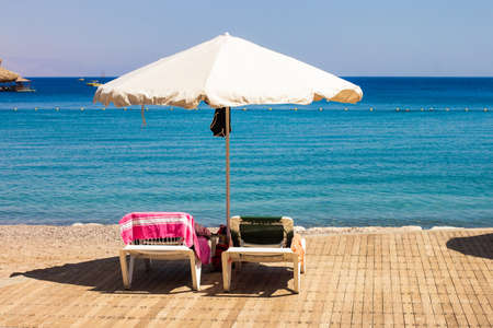 hotel resort area beach deck chair and umbrella lunge furniture summer time vacation season concept scenic view on Red sea waterfront without people here