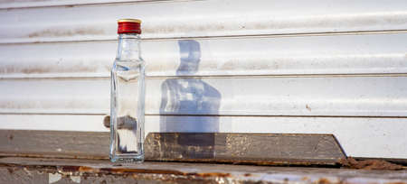 alcohol empty bottle in dirty slums backstreet white wall background