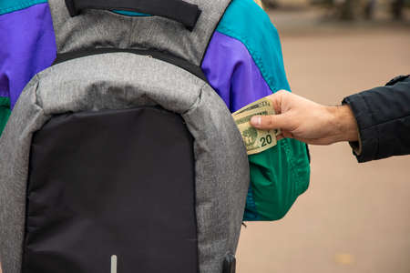 stealing money from bag criminal action concept street photography back to camera background view 版權商用圖片