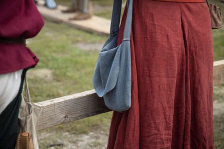 middle ages reconstructed woman fashion dress and handbag medieval festival reportage photo textile cloth center of foreshortening