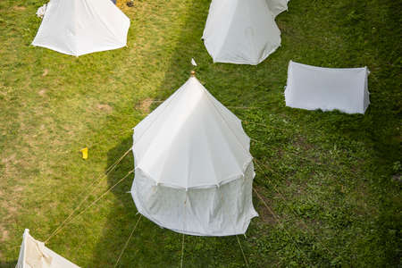 historical festival white tent middle age time reconstruction object strategy top view concept foreshortening of camp site without people here on bright grass meadow under sun light