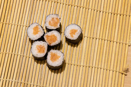 Asian cuisine sushi rolls maki with salmon raw fish home made food photography objects on wooden carpet background on table concept picture copy space
