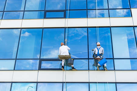 window cleaner two person back to camera dangerous work at height outside of building glass exterior blue and white wall background space