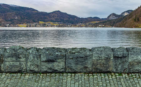 moody European village outskirts landmark scenic view in autumn season November month time Alps mountain and small houses background calm lake water surface and decorative stone wall foreground