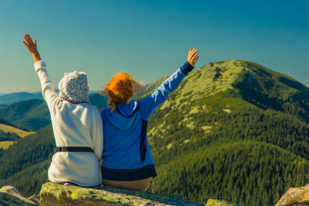 two girls posing back to camera on top of Carpathian mountains gorgeous summer landscape background scenic view travel life style concept picture Zdjęcie Seryjne