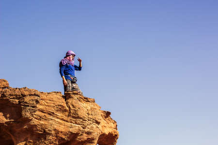 adventure and travel concept bright photography of young girl portrait who looking for the horizon from edge of the cliff of top high rock view point in Wadi Rum Middle East desert, copy space text