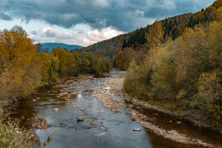 autumn mountain forest dramatic landscape October time scenic view with rocky river stream moody nature environment space