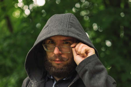 serious man in hoodie close portrait photography of middle adult male person with beard and glasses on the street park outdoor area bokeh unfocused background space