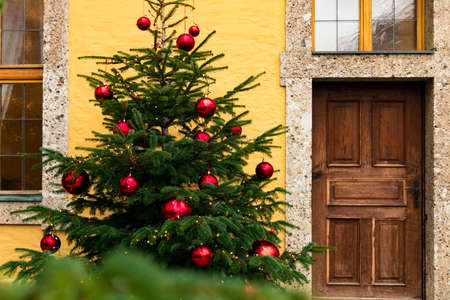 Christmas tree winter holidays street urban view background with festive toys and wooden door object Banque d'images