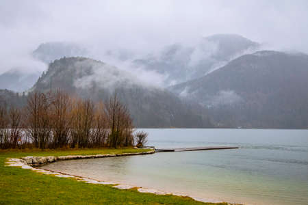 misty landscape morning foggy weather time autumn September season in Norway scenic view with lake shore line and mountains in smoke background