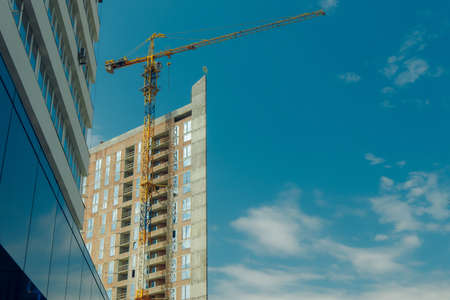 high tower construction building industry landmark picture foreshortening from below with crane and clear blue sky background space for copy or your text here